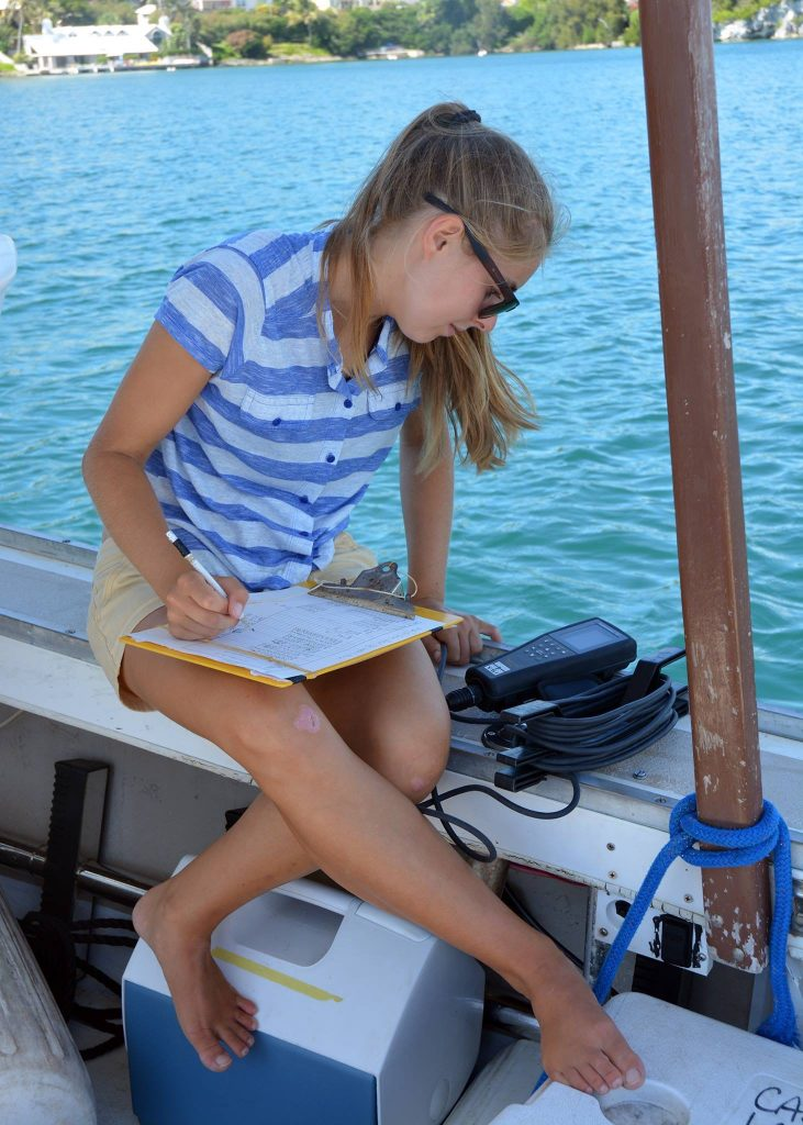 Anna sat on the side of a boat writing down measurements from the piece of equipment she is looking at.