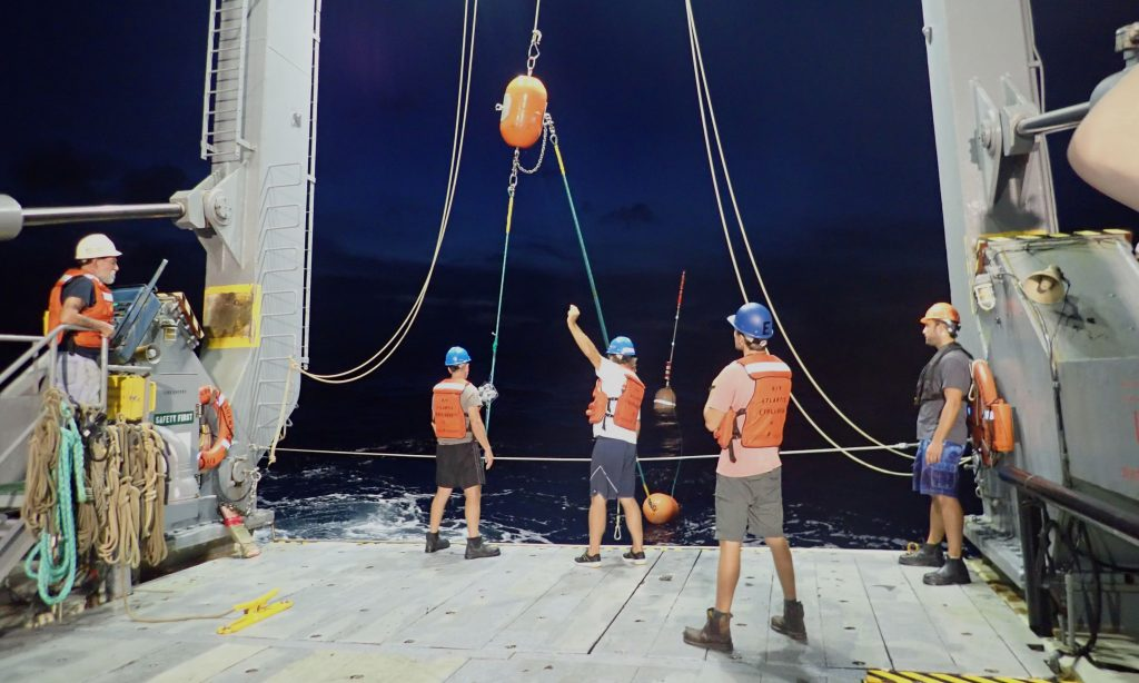 Photo of people deploying equipment from the back of a research vessel at night.