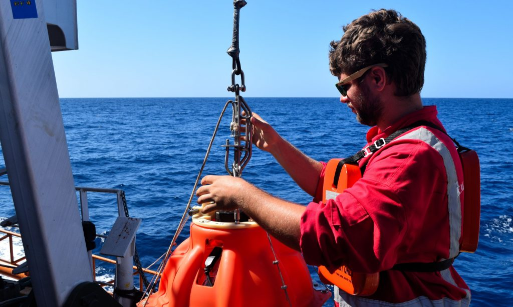 Tim Greenfield prepares an ocean bottom seismometer for deployment, connecting it to a winch ready for lowering into the ocean.
