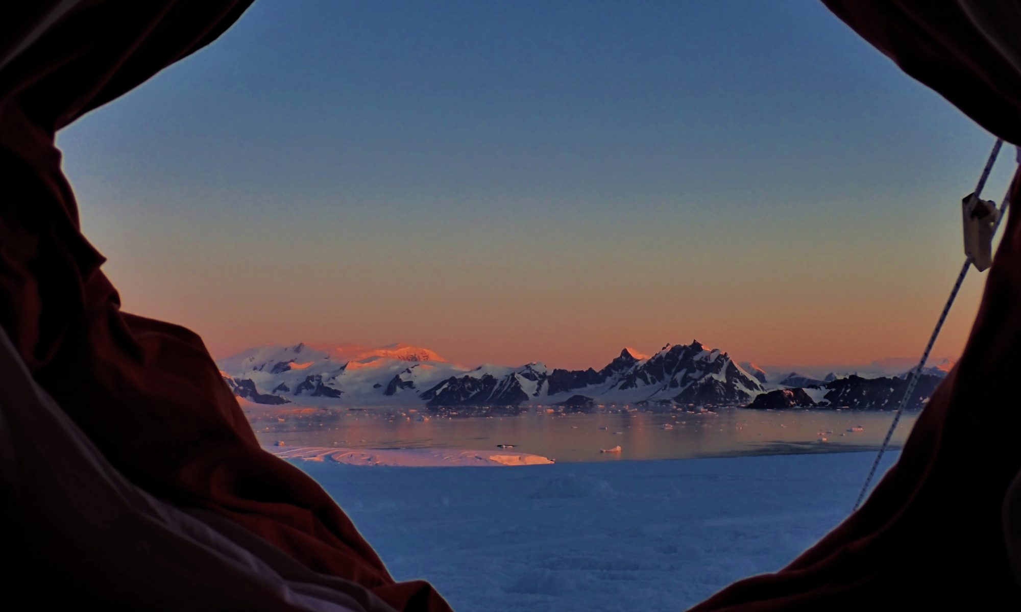 A photo of sunset lit peaks behind an ice-filled bay, taken from the opening of a red canvas tent.