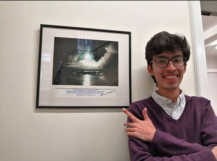 Image of Hassan smiling and standing in front of a photo of Apollo 17 launching