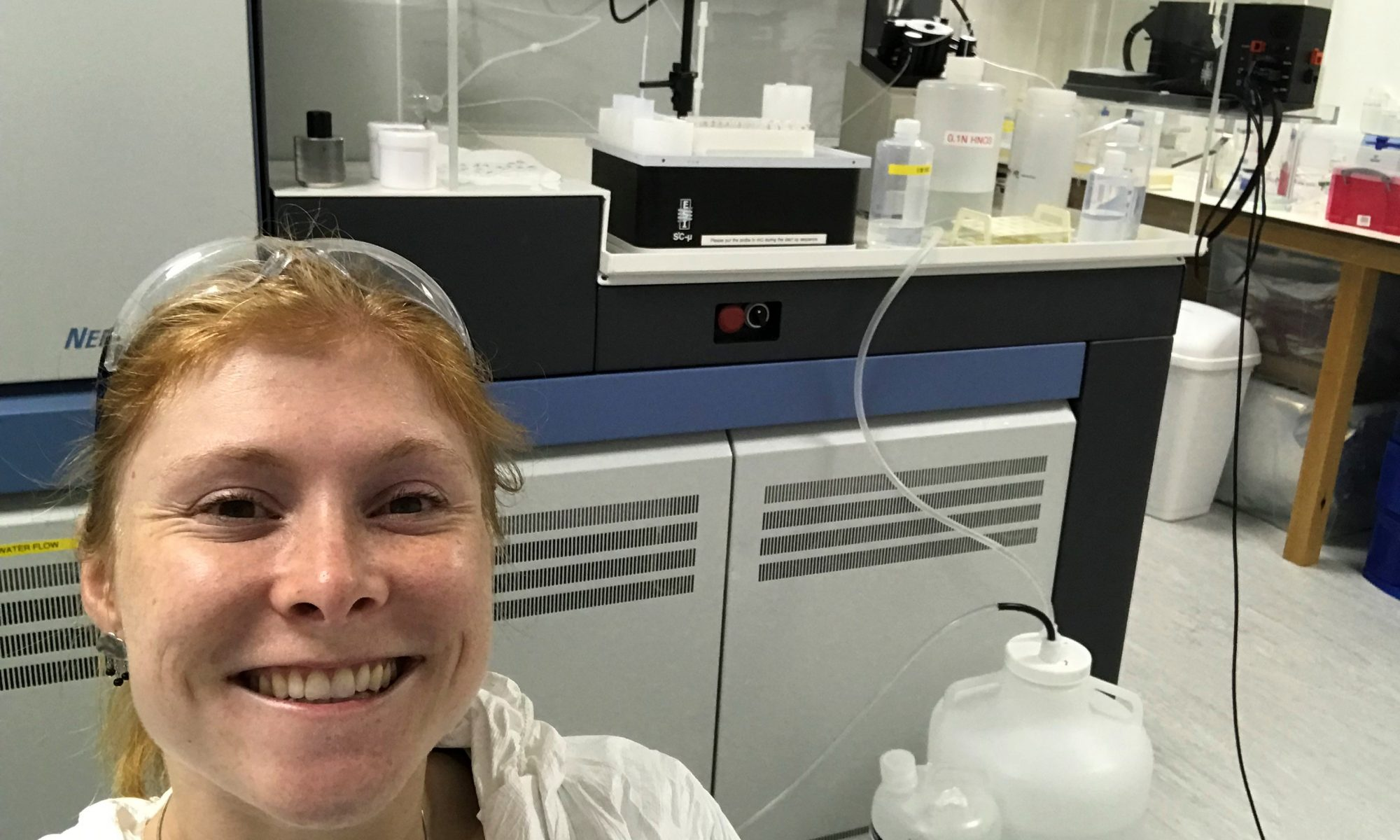 Carrie in the lab, wearing protective gear and stood in front of a mass spectrometer