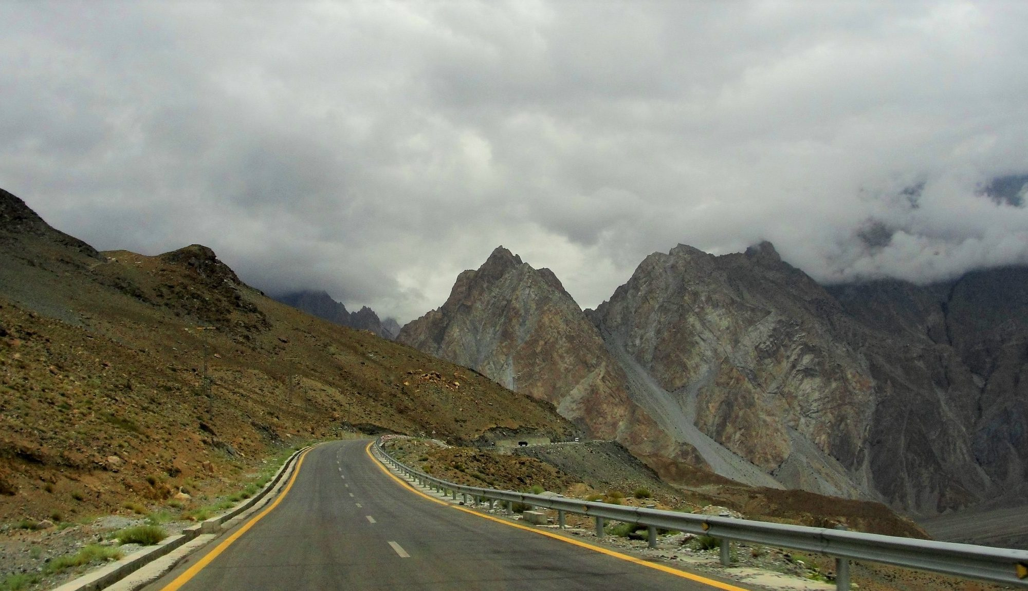 Image of mountainous backdrop, with winding road extending into the distance